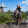 Moeder en dochter op de fiets op dijk met molens